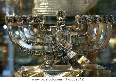 TIBERIAS ISRAEL - FEBRUARY 26 2017: Chanukah candlestick with a jug of oil in the window of the souvenir shop. Chanukiah contains stylized houses of Jerusalem