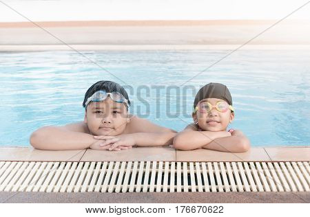 cute asian girl and fat boy smile in swimming pool concept sport and vacation
