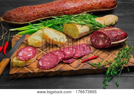 Small antipasto sandwiches from baggetta bread raw smoked sausage on board knife. Ingredients for sandwiches with sausage thyme rosemary fresh onions red hot peppers. Dark black wooden background