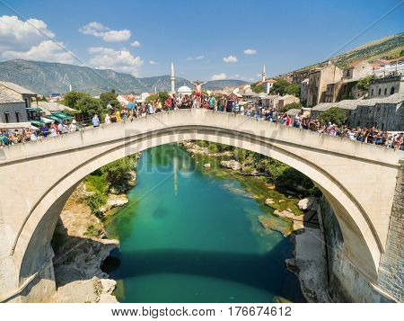 MOSTAR, BOSNIA - AUGUST 2016: People gathered at Old Bridge for jumping in the  Neretva river in Mostar, Bosnia and Herzegovina.