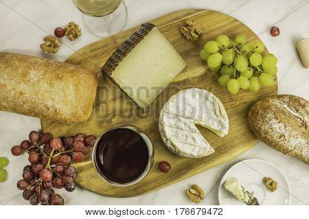 An overhead photo of a glass of red wine with cheese, white and rye bread, purple and white grapes, and walnuts, at a wine pairing