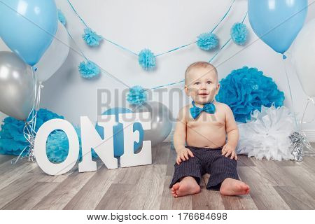 Portrait of adorable Caucasian baby boy in dark pants and blue bow tie celebrating his first birthday with letters one and balloons sitting on wooden floor in studio