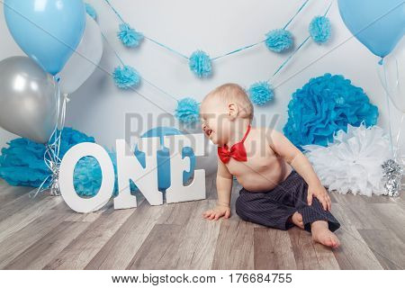 Portrait of crying screaming unhappy Caucasian baby boy in dark pants and red bow tie on his first birthday with letters one and balloons sitting on wooden floor in studio