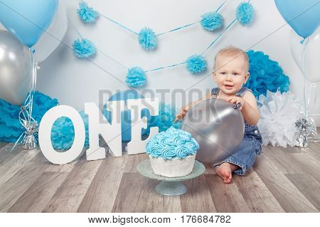 Portrait of cute adorable blond Caucasian baby boy with blue eyes in jeans overall holding grey balloon celebrating his first birthday letters word one cake smash in studio