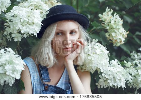 Closeup portrait of beautiful Caucasian teenage young blonde model girl woman in blue tshirt jeans romper black hat sitting among large white flowers on summer day