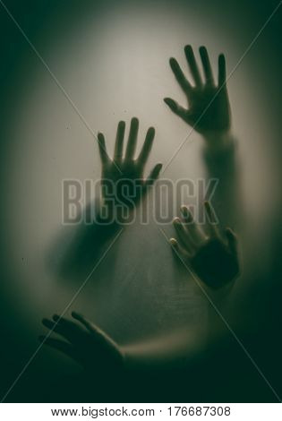 Horror hands. Silhouettes through glass