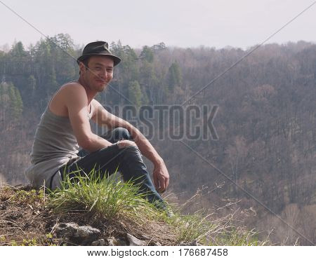 Portrait of Handsome Man in hat at mount near forest, telephoto