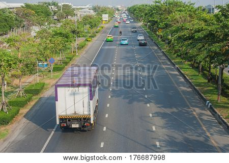 View of city road or street with green tree from overpass.