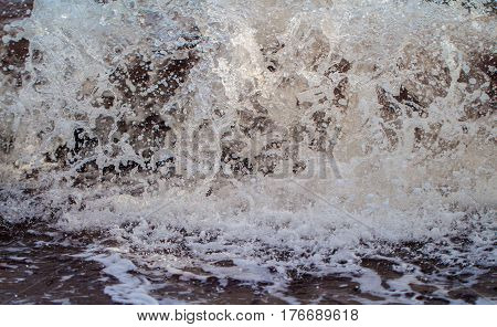 Sea wave with splashes and foam. Shallow water surf of high tide. White water splashes and drops. Hard wave over sand beach. Oceanic power concept. Seaside danger photo. Splashy seawater motion