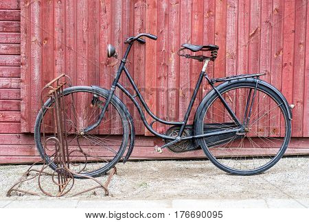 old retro antique black men's bicycle parked up of red wooden fence photographed from the side
