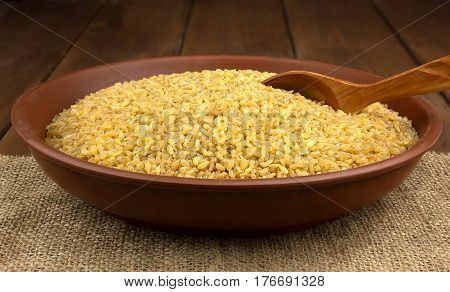 Dry bulgur wheat in a clay bowl with spoon on the sacking