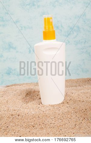 suntan spray on the sand on white bottle