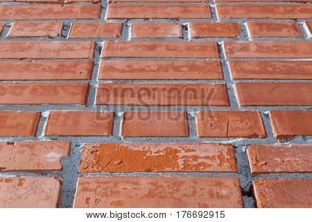 Wall of red brick. The pattern of bricks and joints between them. Some of the bricks with spots visiblename and cracks.