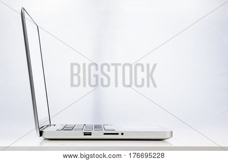 Modern laptop computer on abstract business background, side view