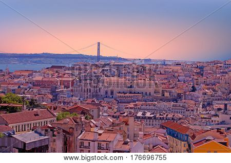 Aerial view with colored houses and the 25 abril bridge in Lisbon Portugal at sunset