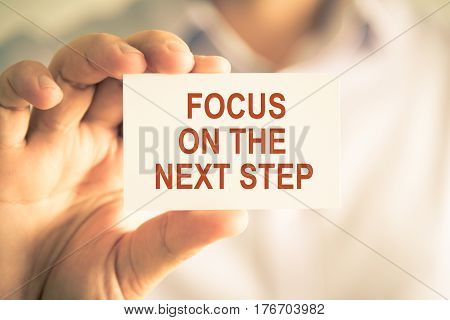 Businessman Holding Focus On The Next Step Message Card