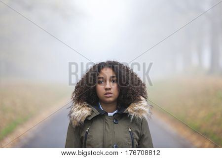 Outdoor portrait of beautiful mixed race African American girl teenager female child outside in  a park on foggy day