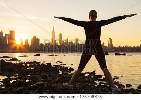 Silhouette of a young woman or girl exercising at sunrise in front of the New York City Skyline