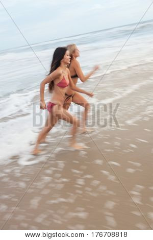 Motion blurred photograph of young women girls in bikinis running on a beach