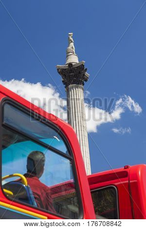 Tourist on red London double decker bus looking at Nelsons Column in Trafalgar Square London, England