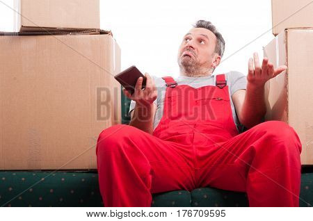 Mover Man Sitting On Couch Holding Phone And Gesturing