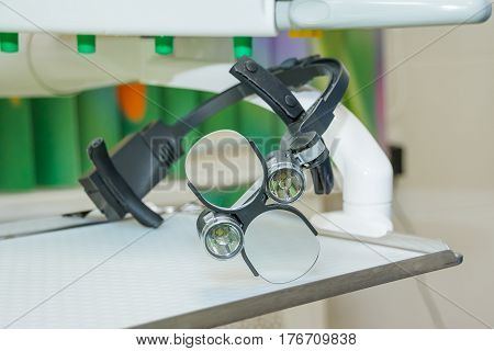 the dental binocular loupes on white tablel in dental office. Dentist goggles, protective glasses in dentist's office. Dentistry. Dental loupes.