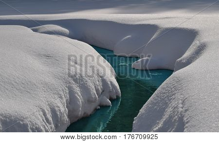 Uncovered Siberian river with blue water in snow valley. Novosibirsk Siberia Russia.