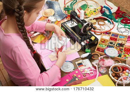 girl sews doll clothes, top view, sewing accessories top view, seamstress workplace, many object for needlework, handmade and handicraft