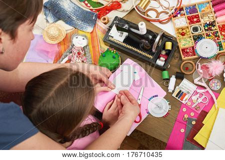 mother teaching daughter to sew doll clothes, top view, sewing accessories top view, seamstress workplace, many object for needlework, handmade and handicraft