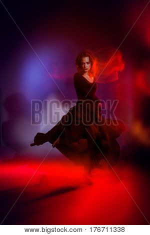 Art concept. Beautiful young woman dancer performing tango at studio.