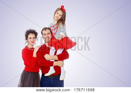 Happy young family dad mom and a little girl in bright red outfits . Dad holds daughter on hands.Purple gradient background.