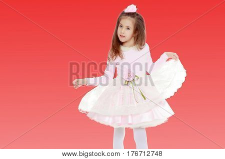 Dressy little girl long blonde hair, beautiful pink dress and a rose in her hair.She plays with her floors for her dress.