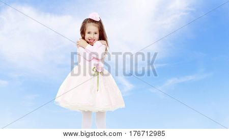 Dressy little girl long blonde hair, beautiful pink dress and a rose in her hair.She got cold.On the background of summer blue sky and fluffy clouds.