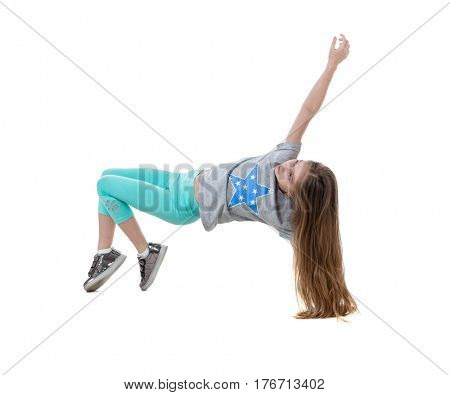 Long-haired girl dancing and moving swiftly, wearing green leggings, isolated on white background