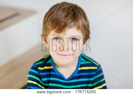 Portrait of little cute school kid boy colorful school uniform fashion clothes. Child smiling and looking at the camera. Happy blond boy