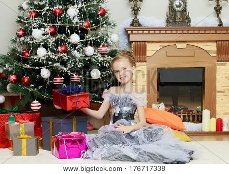 Beautiful little girl in a dress of Princess around the Christmas tree.Girl holding on outstretched hand a box of beautifully packaged gift.