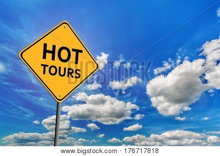 Background of blue sky with cumulus clouds and yellow road sign with text Hot Tours