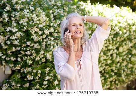 Older Woman Talking On Phone With Hand To Head Outside