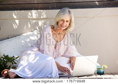 Smiling Older Woman Sitting Outside With Laptop