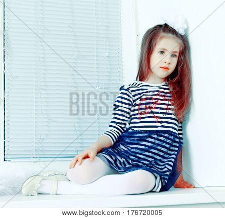 Little girl in blue striped dress and a white bow on her head.She sits at the window with sad eyes.Creative toning of a photograph.