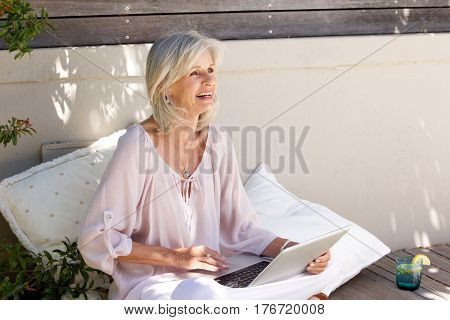 Older Woman Sitting Outside Working On Laptop