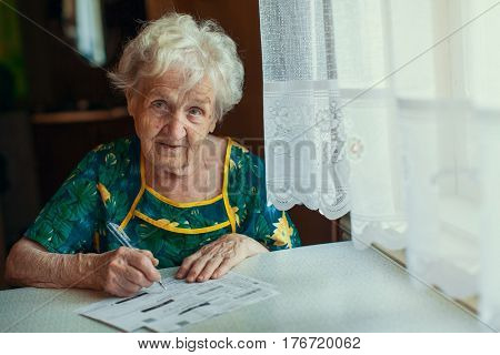 Elderly woman fills out utility bills.