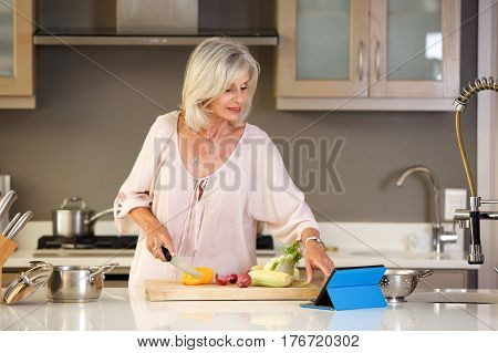 Older Woman In Kitchen Reading Recipe On Tablet
