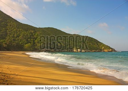Caribbean beach with tropical forest. Tayrona National Park. Colombia. Tayrona National Park is located in the Caribbean Region in Colombia. 34 km from the city of Santa Marta is one of the most important natural parks of Colombia.