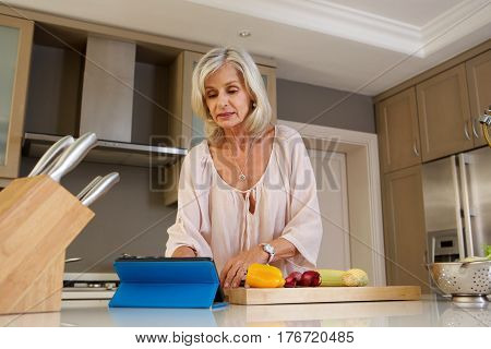 Older Woman Reading Recipe In Kitchen On Tablet