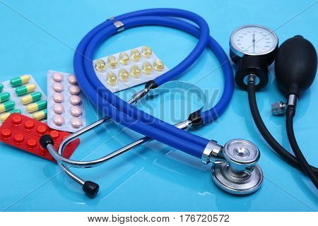 Stethoscope, red heart, asorted pils and medical equipmenton on blue background.