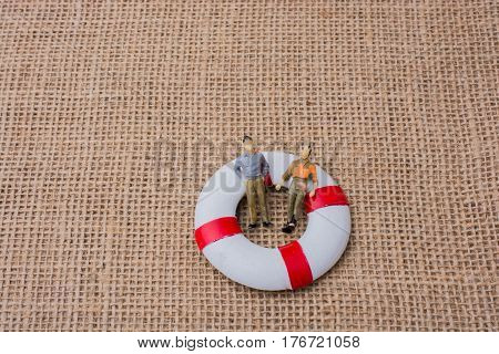 Little figurine men in a life preserver on life on canvas