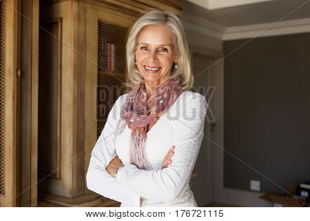 Beautiful Older Lady Smiling With Arms Crossed At Home