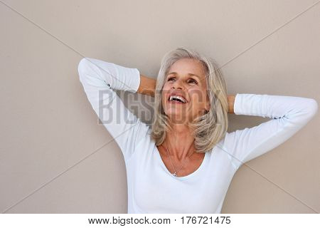 Portrait of beautiful older woman leaning with hands behind head poster