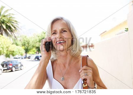 Smiling Woman On Phone Outside On Sidewalk